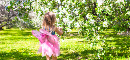 Adorable little girl in blossoming apple tree garden at may