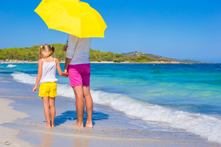 sunstroke: Little girl and young dad at white beach with yellow umbrella Stock Photo