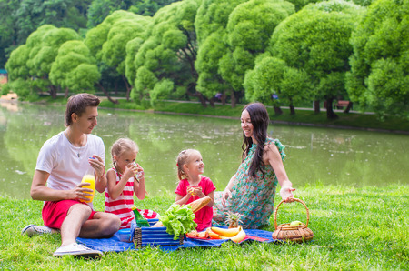 picnicking: Happy young family picnicking outdoors near the lake Stock Photo