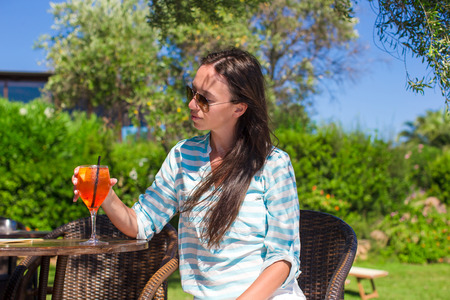Young beautiful woman with cocktail in oitdoor cafe at exotic resort photo
