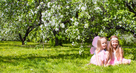 Adorable little girls in blossoming apple tree garden at spring day