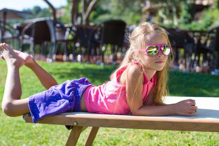 Schattig klein meisje op het strand lounger buitenshuis