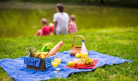 picnic food: Happy family picnicking in the park