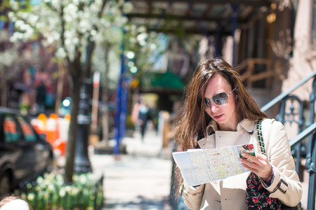 Young woman with map in historic district of West Village