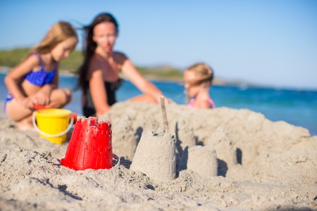 Happy family playing with beach toys during tropical vacation Stock Photo