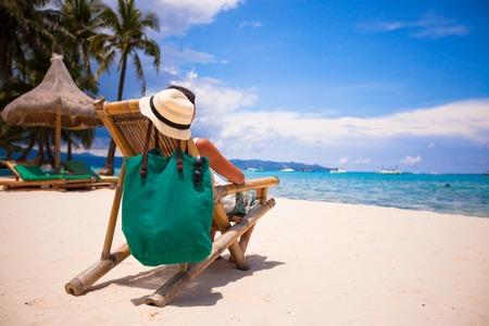 Schöne Mädchen Entspannung in hölzernen Stuhl am Strand
