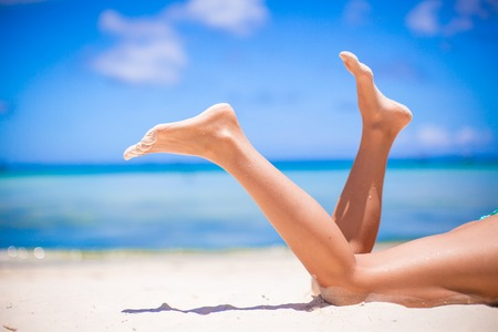 Female beautiful smooth legs on white sand beach 스톡 콘텐츠