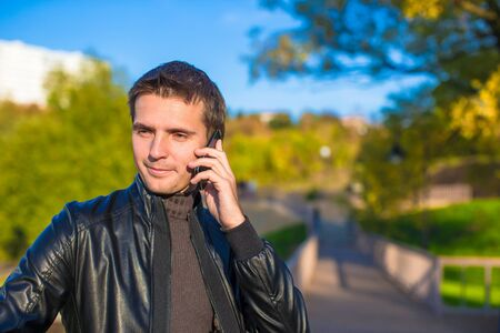 outoors: Young man with talking by phone outoors