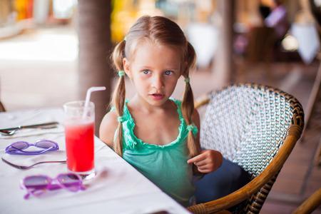 honey blonde: Adorable little girl having breakfast and drinking fruit cocktail