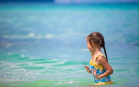 little girl smiling: Little happy girl at swimsuit having fun in clear sea Stock Photo