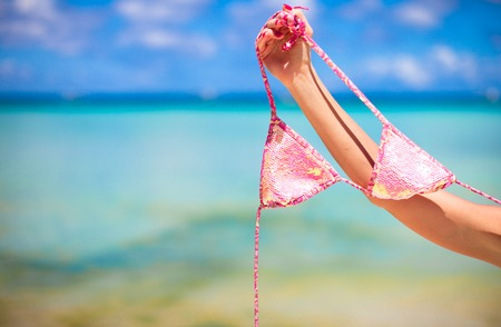 Woman leg holding pink bra isolated on exotic background