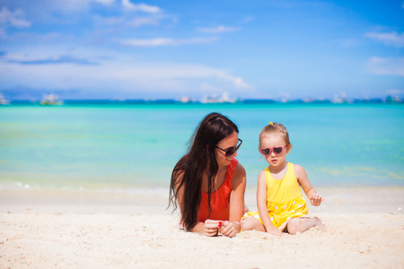 Adorable little girl and happy mom during tropical beach vacation photo