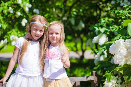 Little adorable girls at blossom trees park photo