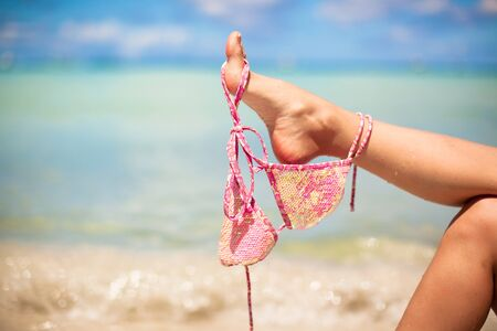 Woman leg holding pink bra isolated on exotic background photo