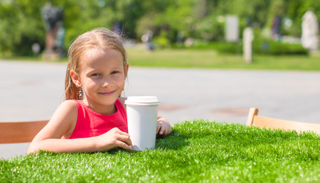 Little adorable girl at outdoor cafe on warm summer day photo