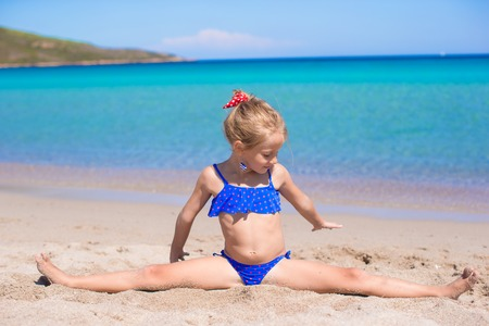 Adorable little girl have fun on tropical white sandy beach