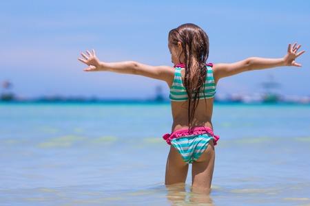 petite fille avec robe: Bonne petite fille en se amusant, la natation et le saut à l'eau peu profonde
