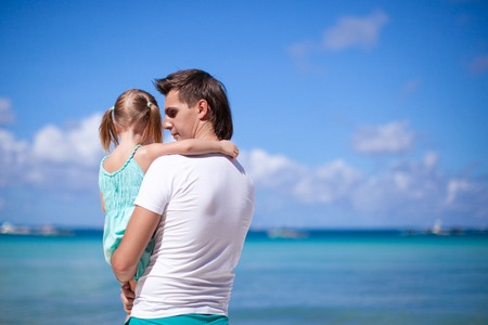 Happy dad and his adorable little daughter at tropical beach