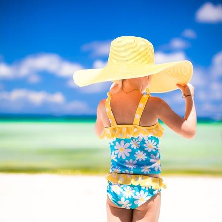 yellow bikini: Little girl in big yellow hat on white sandy beach
