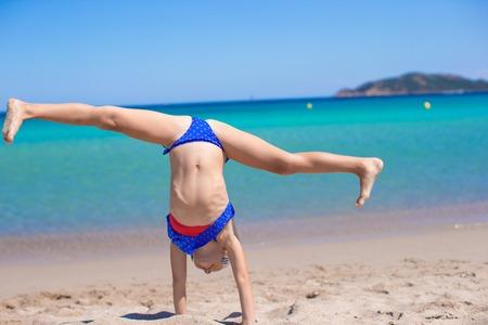 Adorable little girl on tropical white sandy beach