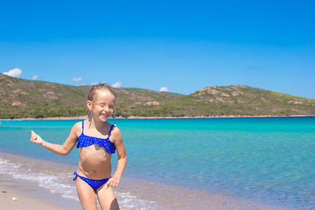 young gymnast: Adorable little girl have fun on tropical white sandy beach