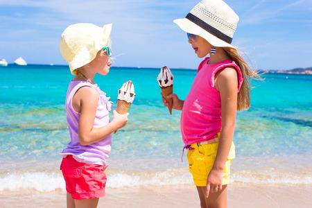 comiendo helado: Las ni�as adorables que comen el helado en la playa tropical