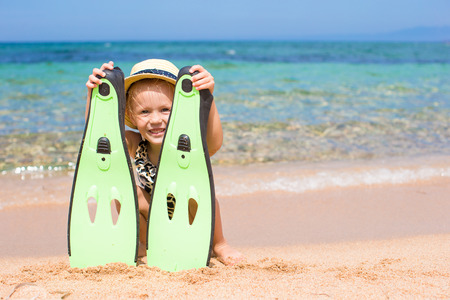 snorkling: Little girl with flippers and goggles for snorkling on the beach Stock Photo