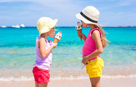 Little adorable girls eating ice cream on tropical beach