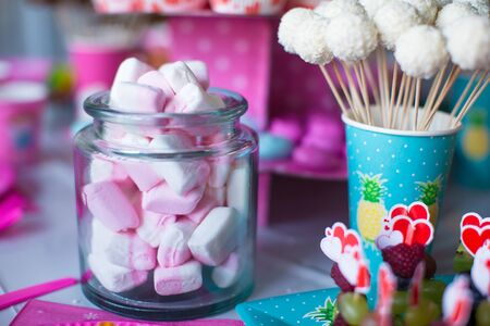 childrens birthday party: Marshmallow, sweet colored meringues, popcorn, custard cakes and cake pops on table