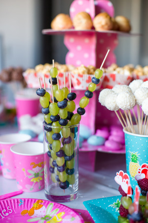 childrens birthday party: Canape of fruit, white chocolate cake pops and popcorn on sweet childrens table at birthday party Stock Photo