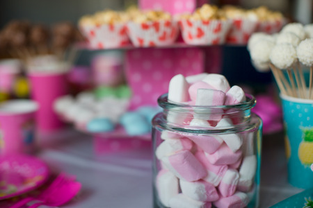 Marshmallow, sweet colored meringues, popcorn, custard cakes and cake pops on table