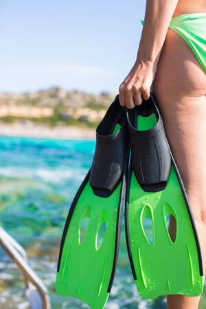 fins: Diving goggles, snorkel and snorkeling fins at woman hands