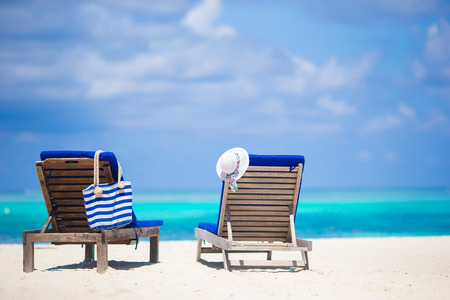 tropical beaches: Lounge chairs with bag and hat on tropical beach at Maldives