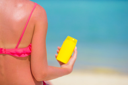 suncare: Beautiful young woman holding a suncream lying on tropical beach