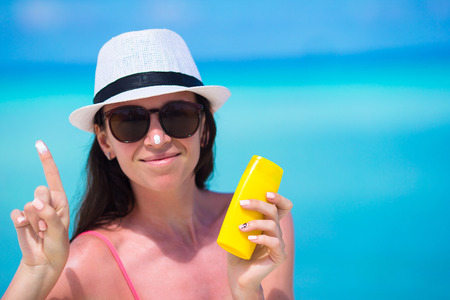 suncare: Young happy woman applying suntan lotion on her nose on white beach
