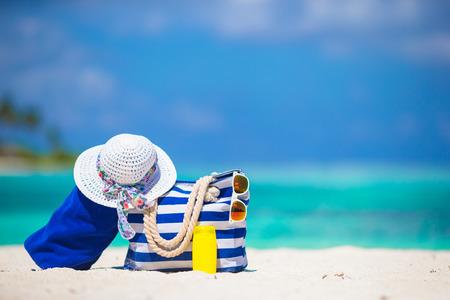 Blue stripe bag and towel, straw white hat, sunglasses, sunscreen bottle on exotic beach Archivio Fotografico