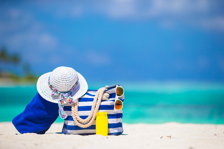 Blue stripe bag and towel, straw white hat, sunglasses, sunscreen bottle on exotic beach Standard-Bild