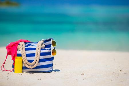swimsuit: Blue bag, swimsuit, sunglasses and suncream on white beach Stock Photo