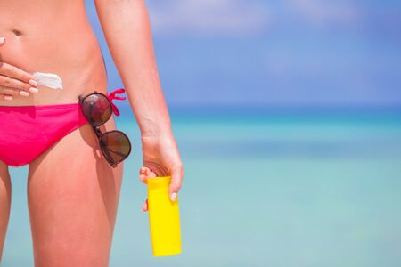 suncare: Young woman applying stomach with sunscreen on white beach Stock Photo