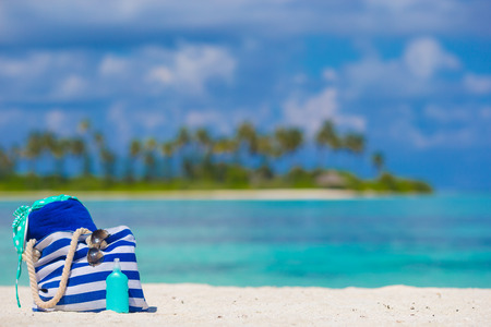 palmtrees: Stripe bag, blue towel, sunglasses, sunscreen bottle and swimsuit background turquoise water and green palmtrees