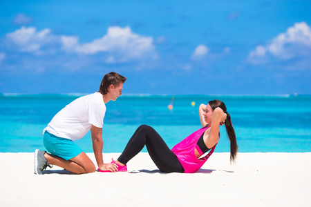 beach feet: Young couple do abdominal crunches on white beach during vacation Stock Photo