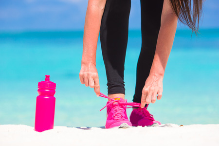 drink at the beach: Fitness and healthy lifestyle concept with female model tying laces on sneakers