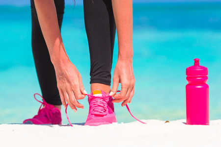 the female: Fitness and healthy lifestyle concept with female model tying laces on sneakers