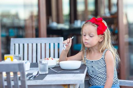honey blonde: Adorable little girl eating porridge on breakfast at outdoor cafe