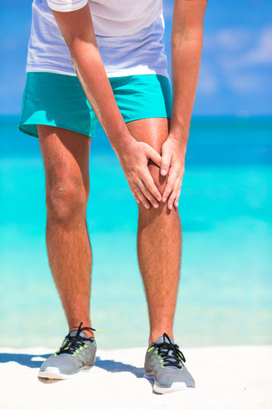 contracture: Male athlete suffering from pain in leg while exercising on white beach