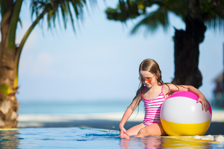 beach wrap: Smiling adorable girl playing with inflatable toy ball in outdoor swimming pool Stock Photo
