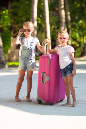 portmanteau: Little adorable girls with big suitcase on tropical white beach during summer vacation
