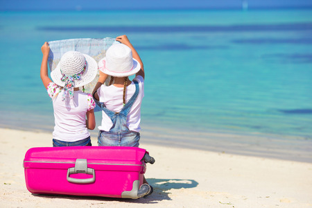 Little girls with big suitcase and map at tropical beach