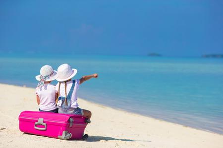 夏休みの間に熱帯白いビーチに大きなスーツケースでかわいい女の子