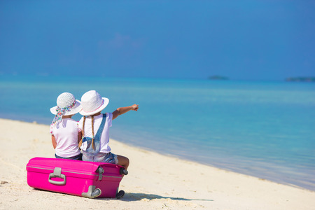 summer holiday: Little adorable girls with big suitcase on tropical white beach during summer vacation